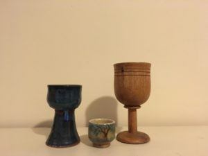 Photograph of three chalices: one smaller blue pottery, one very small offering cup with a tree in glazes, and one carved from wood.