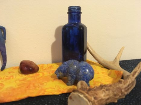 Photograph of several decorative altar items: a carved lapis bear, an antler, a large carnelian stone, and a cobalt glass bottle.