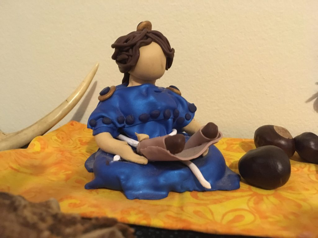 Photograph of polymer clay figure of a woman reading a scroll, with several horse chestnuts beside her, and the tip of an antler in the background