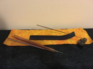 Photograph of incense stick holder, loose sticks, and lighter.