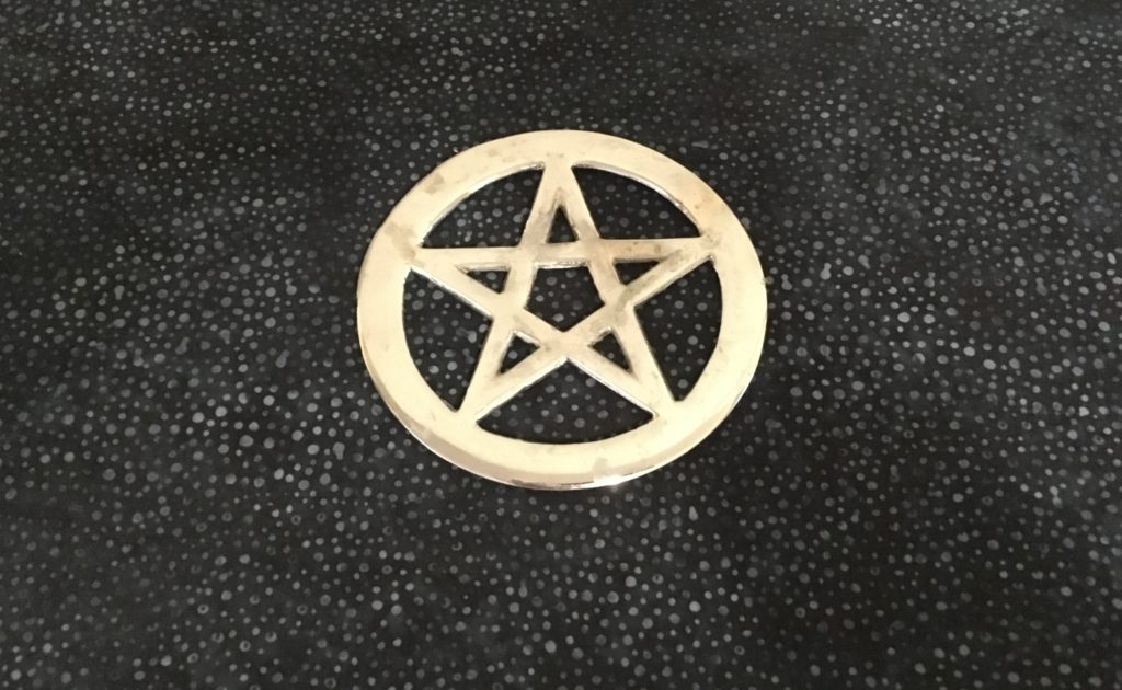 Photograph of silver metal pentacle on blue and gray altar cloth