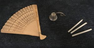 Photograph of wooden fan, candle snuffer, and three small candles for lighting other candles.