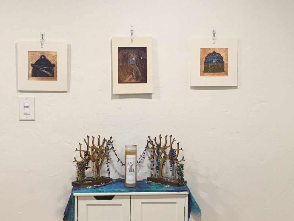 Venus and Jupiter shrine: two wooden trees holding necklaces and jewellery on a small set of shelves with a large glass-enclosed candle in the middle and a blue-green silk altar cloth. Three prints hang above.