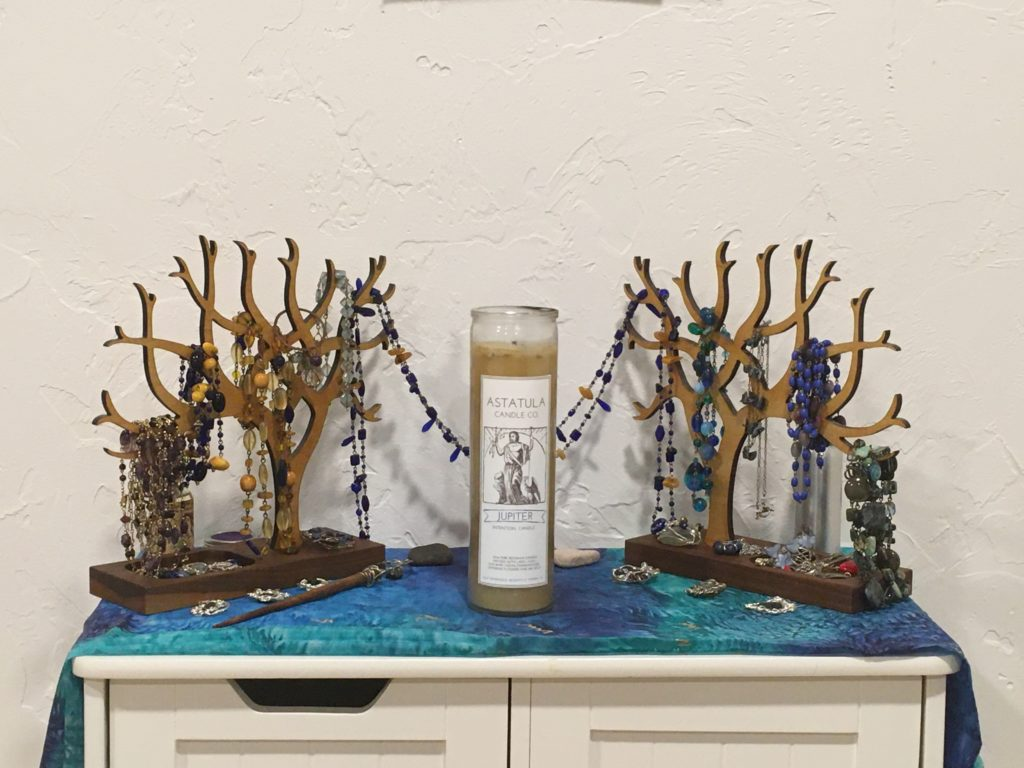 A closer image of the shine itself, showing necklaces draped and coiled on wooden jewellry trees, a glass-enclosed candle, and a few other items.