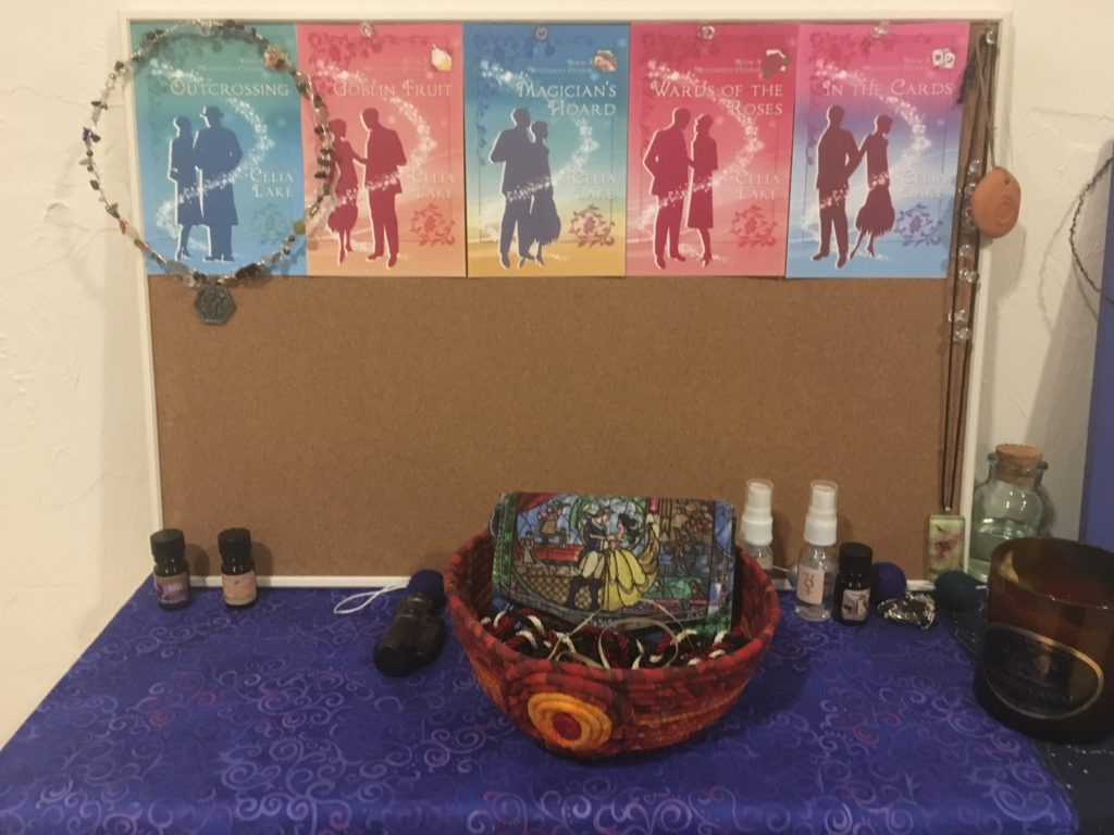 Writing shrine with corkboard with book covers pinned to it, along with a few necklaces. A red cloth bowl sits in the center on a blue cloth, with a wallet with a stained glass image from Beauty and the Beast.. There are several small perfume and spray bottles.