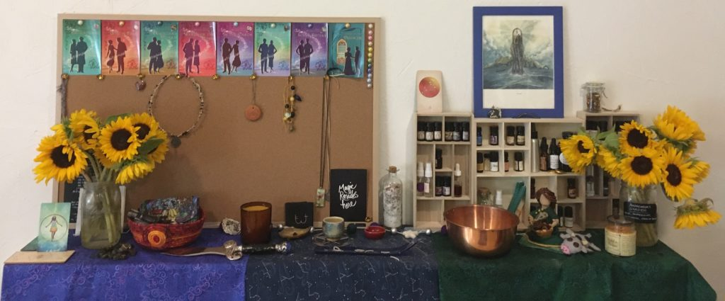 A view of my shrine, as of August 2020: bookshelves with altar cloths of blue, black, and green dividing the space, a bulletin board with cover images of books and jewellery hanging from it, various bowls for offerings and ongoing workings, wooden shelving holding bottles of oils and perfumes. Two bright golden vases of sunflowers are at either end.